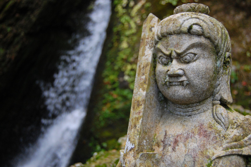 angry demon statue by the waterfall