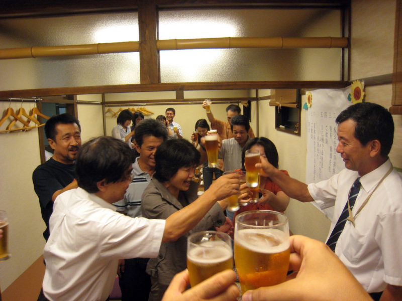 "In Japan, enkai proceed in the following fashion: First, a person annouces the beginning of the enkai, and invites the most important person to speak a few words (in this case, the principal). The important person makes a speech, and then everyone stands up, raises their glass, and yells ""Kampai!"" which means cheers! Glasses are clinked and the party commences."